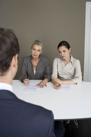 2 businesswomen interviewing man Stock Photo