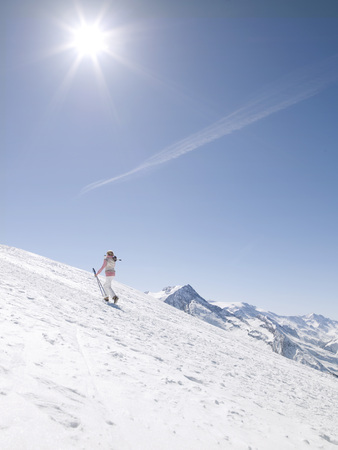 woman walking up mountain with skis