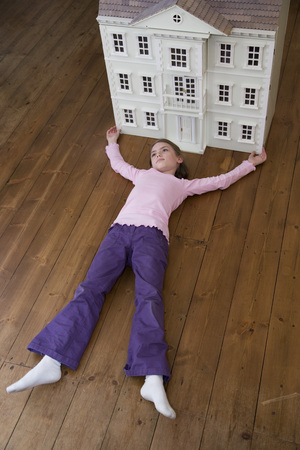 trusted: A girl lying in front of her dollhouse.