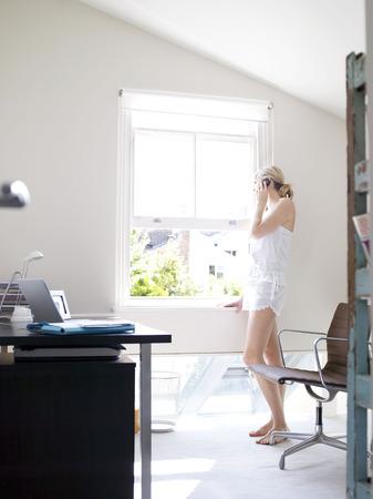Femme au téléphone dans un bureau ensoleillé Banque d'images - 86032097