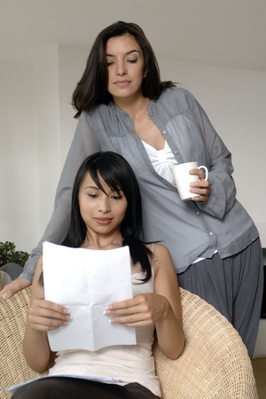Two women reading a letter