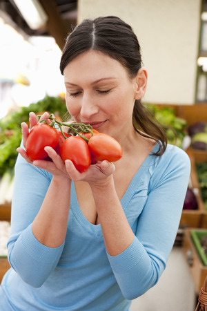 Woman taking smell at fresh tomatoes Stok Fotoğraf - 103176603