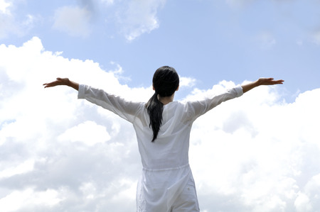 Woman opening her arms against sky Stock Photo