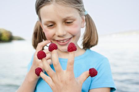 Young Girl Eating Raspberries