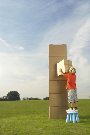 lone boy with box and tower