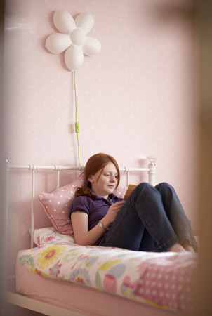 Teenage girl reading in bedroom