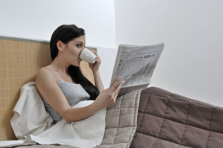 Woman reading paper in her bed Stock Photo