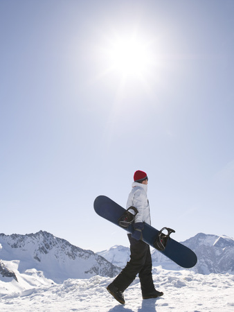 man with snowboard on top of mountain