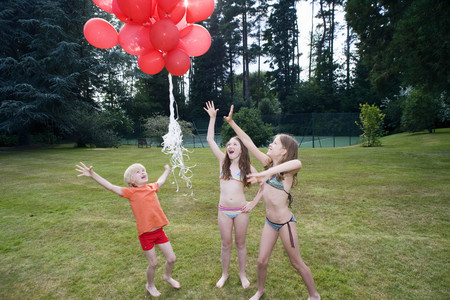 Kids letting red balloons go