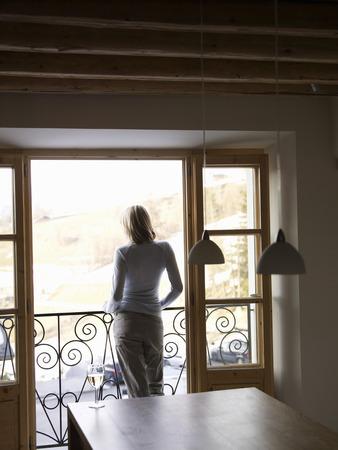 woman standing at open balcony door Banco de Imagens