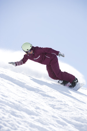 Girl in jumpsuit boarding down hill.