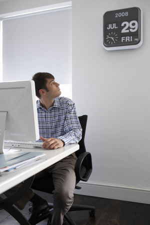 Office worker looking at clock Banco de Imagens
