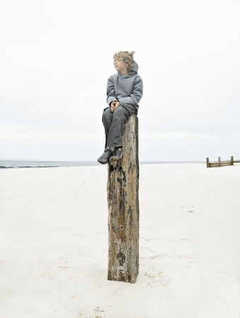 Boy sitting on top of post