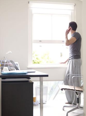 Homme sur téléphone dans un bureau ensoleillé Banque d'images - 86032145