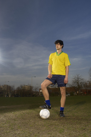 A footballer standing with a ball