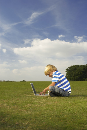 boy on computer in field