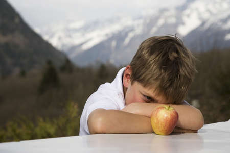 trusted: Boy observing an apple.