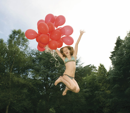 Girl with red balloons jumping in garden Stock Photo