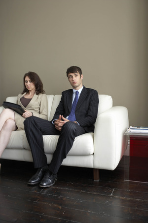 Businessman and woman sitting on sofa Banco de Imagens