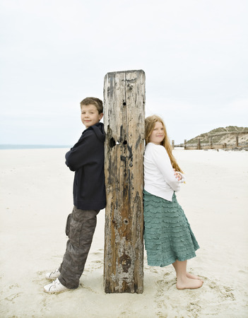 Boy & Girl leaning against post Stock Photo - 86032164