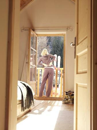 woman sitting on bedroom floor in chalet Stock Photo