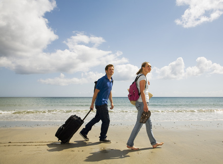 Couple walking on beach With Case