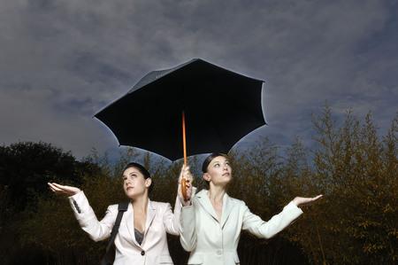 2 women under an umbrella