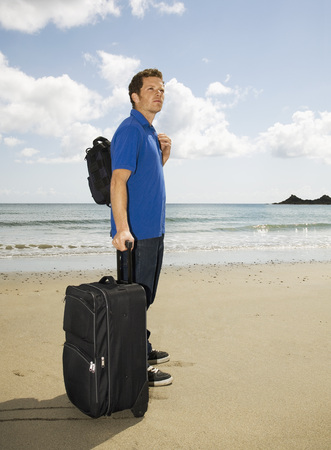 A man on the beach with suitcase