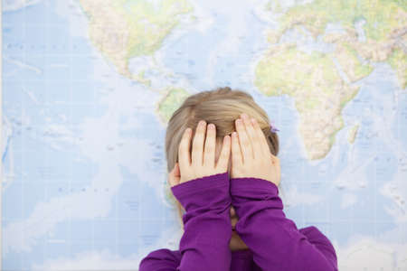 young girl hiding face with hands Stock Photo