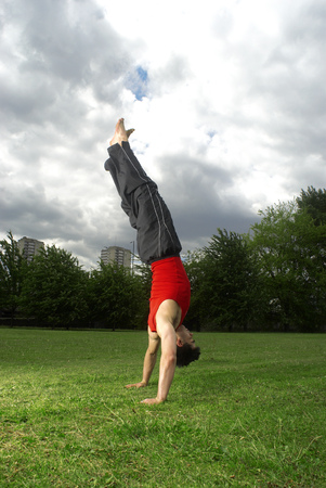 man doing handstand in park Stock Photo