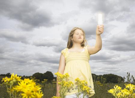 필드의 에너지 절약 전구를 가진 소녀 스톡 콘텐츠