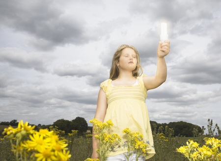Girl with energy saver bulb in field