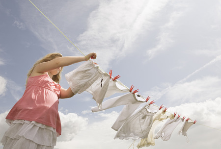 Girl putting clothing on a washing line