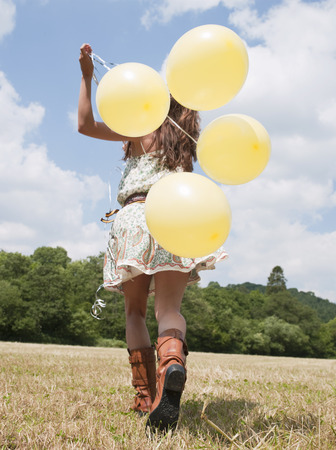 woman running with balloons Stock Photo