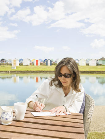 Woman writing at a table Stock Photo