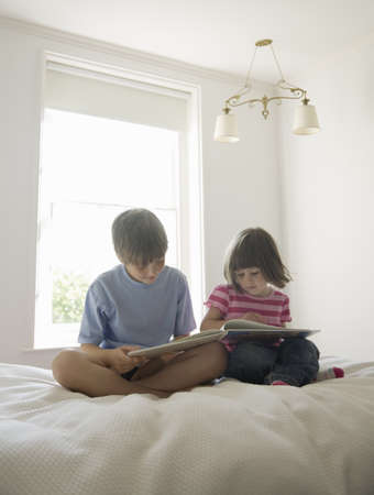 trusted: Boy and Girl reading on bed