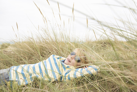 Boy lying with sunglasses in dunes
