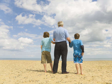 Senior man and 2 boys looking out to sea Stock Photo