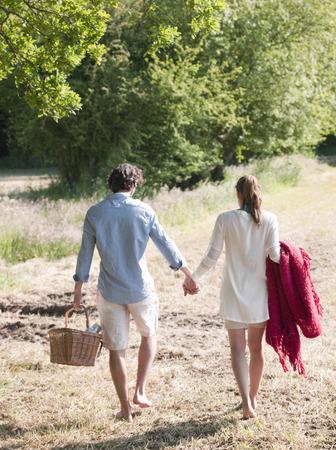 Couple walking in field with picnic Archivio Fotografico