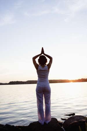 Woman Performing Yoga At Lakeside