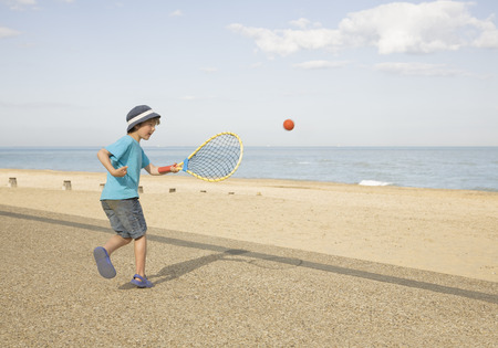 Boy playing tennis on promenade Stock Photo