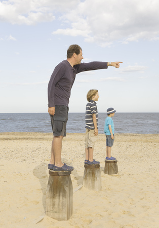 Man pointing with children on groynes