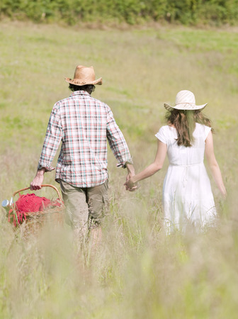 couple in hats walking through meadow Stock Photo