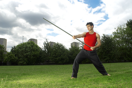 man posing with bow staff