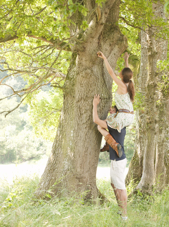 woman on mans shoulders under tree Stock Photo
