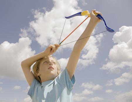Boy firing toy bow