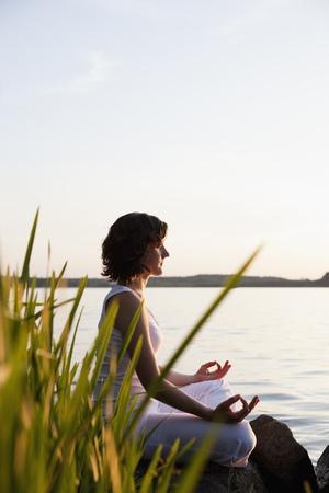 Woman Doing Yoga At Lakeside