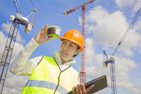 建設現場でのサンプルを表示する女性
