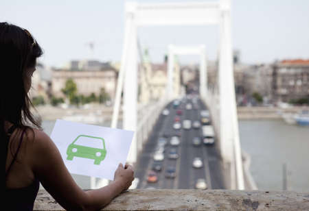 women's issues: Woman holding paper green car