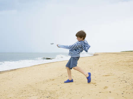 Boy skimming stones out to sea